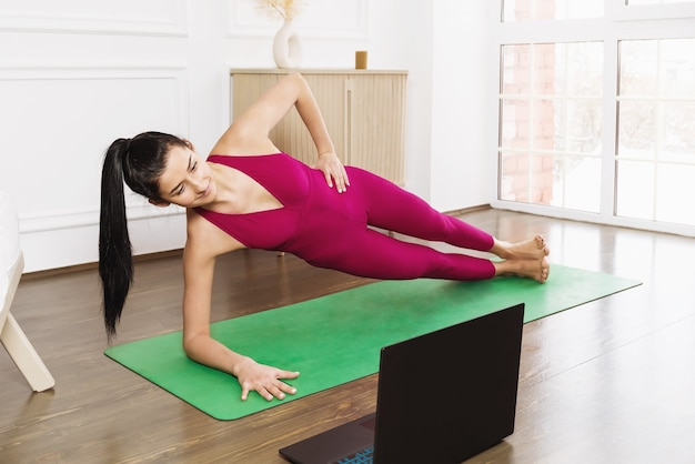 Young beautiful woman in pink sportswear performs side plank exercise during online workout at home