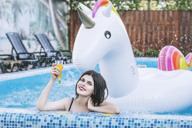 Young beautiful woman in pink swimsuit in the pool at a cocktail  with an inflatable unicorn