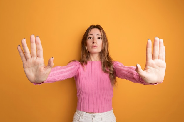 Young beautiful woman in pink top looking at camera with serious face making stop gesture with hands standing over orange background