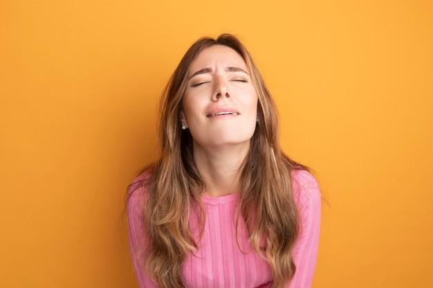 Giovane bella donna in top rosa stanca e annoiata con gli occhi chiusi in piedi sopra l'arancia