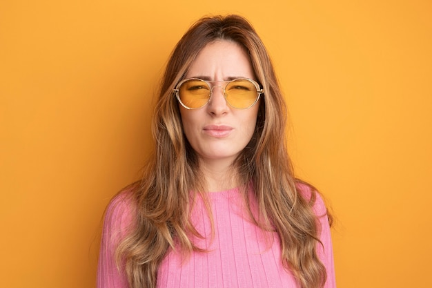 Young beautiful woman in pink top wearing glasses looking at camera displeased frowning standing over orange