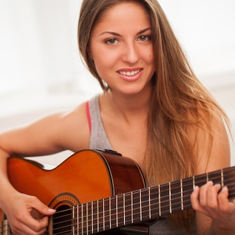 Young beautiful woman playing guitar