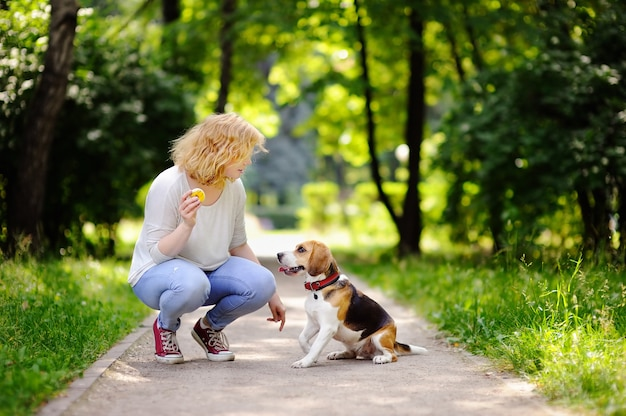 Young beautiful woman playing with beagle dog in the summer park