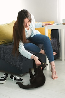 Young beautiful woman playing with her pet black cat