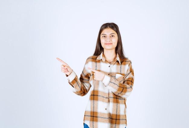 白い壁のどこかを指している若い美しい女性。