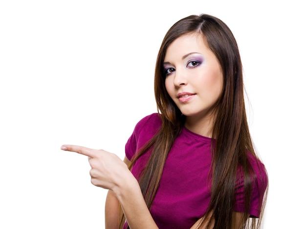 Молодая красивая женщина указывает рукой, изолированной на белом