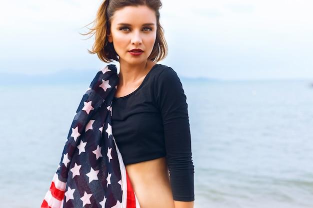 Молодая красивая женщина позирует на берегу моря