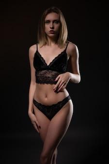 Молодая красивая женщина позирует в черном кружевном нижнем белье