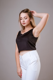 Young beautiful woman posing on a light background in a black blouse and white trousers