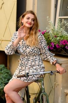 旧市街の通りで自転車の横にポーズをとる若い美しい女性。