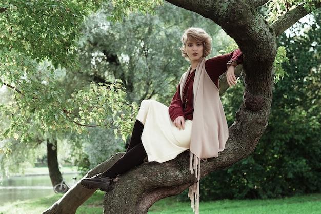 木の上でポーズをとる若い美しい女性。グラマーファッションの肖像画。秋の公園。