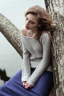 若い美しい女性が木の上でポーズします。グラマーファッションの肖像画。秋の公園。
