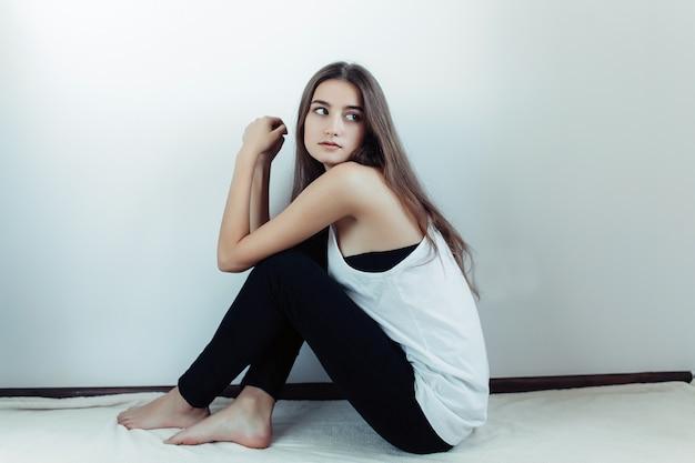 白い壁にポーズをとって若い美しい女性