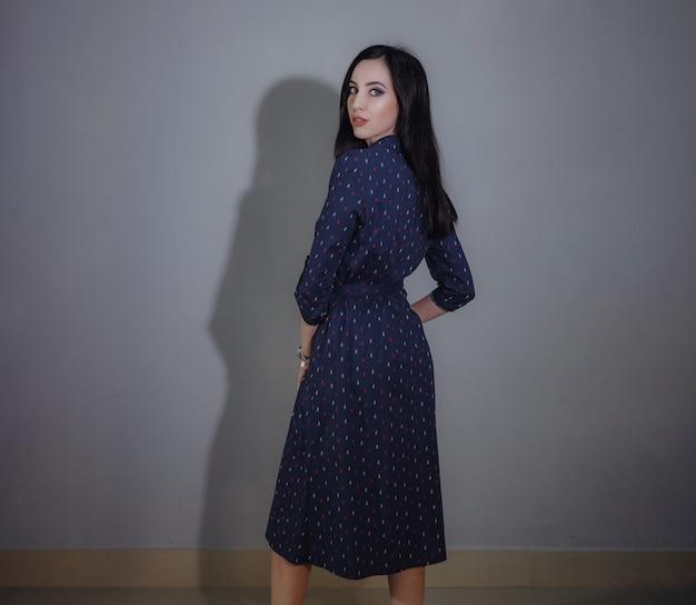 다른 드레스에 회색에 포즈 젊은 아름 다운 여자. 휴일 저녁에 가장 적합한 옵션을 선택합니다.
