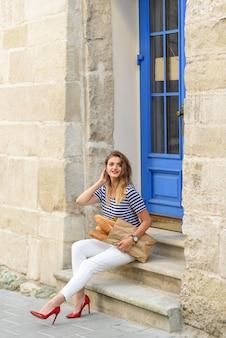 フランスの路上で彼女の手にバゲットを持ってポーズをとる若い美しい女性。