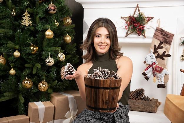 Giovane bella donna in posa con cesto di pigne vicino all'albero di natale