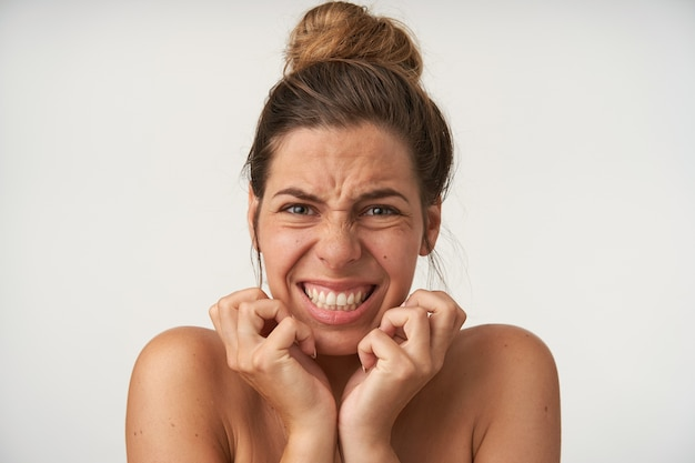 Young beautiful woman posing with frightened face, scaredly holding hands by face, grimacing and showing teeth