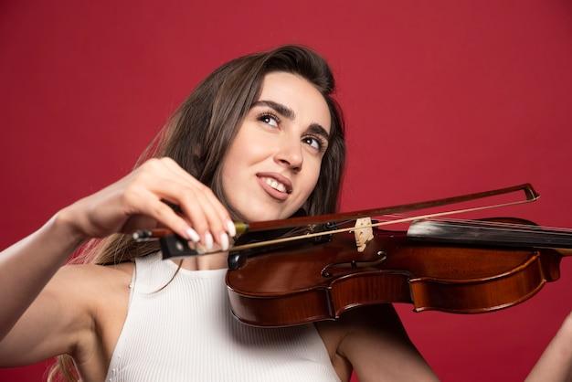 Giovane bella donna in posa con un violino