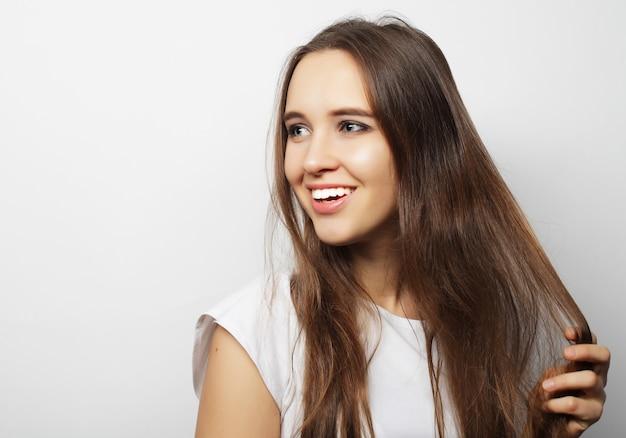 Молодая красивая женщина позирует с белыми футболками, на белом фоне