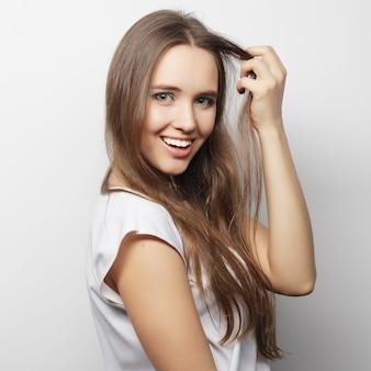 白いtシャツ、ower白い背景でポーズをとって若い美しい女性