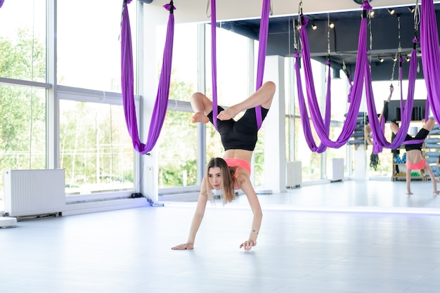Young beautiful woman practice in aero stretching swing hanging upside down. aerial flying yoga exercises practice in purple hammock in fitness club.