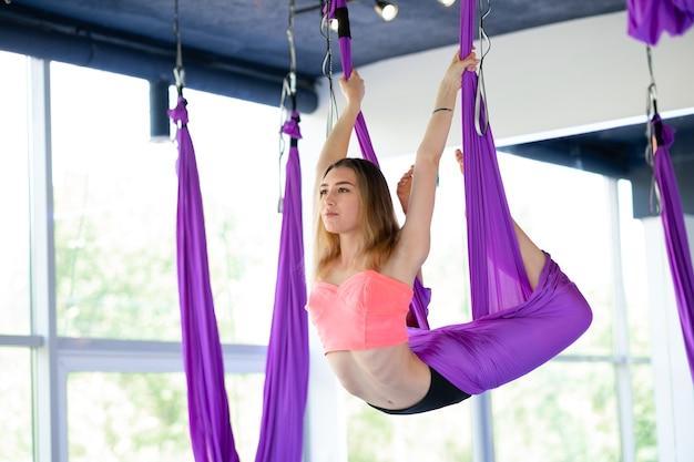 若い美しい女性は逆さまにぶら下がっているエアロストレッチスイングで練習します。空中飛行ヨガの練習は、フィットネスクラブの紫色のハンモックで練習します。