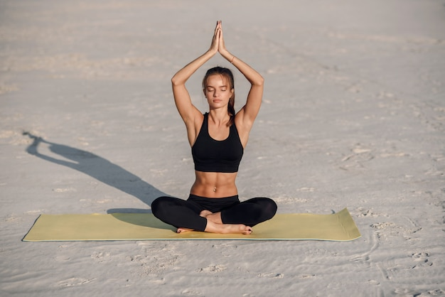 Young beautiful woman practicing yoga on the beach at sunset. healthy active lifestyle concept.