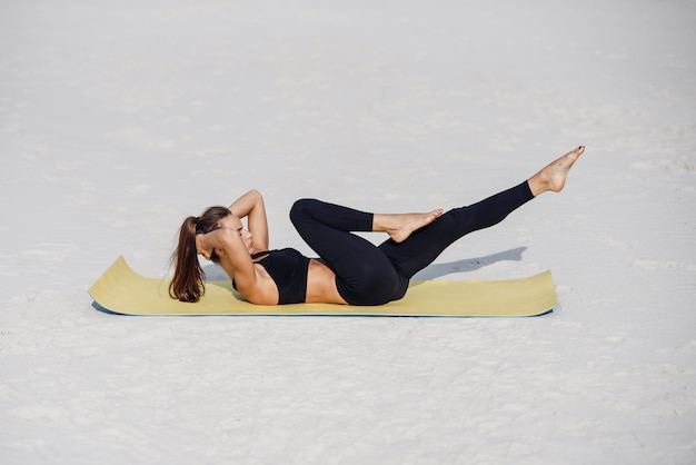 Young beautiful woman practicing yoga, doing press ups exercise on the beach of the sea. fitness yoga and healthy lifestyle concept. beautiful woman in sports wear doing exercise on yoga mat.