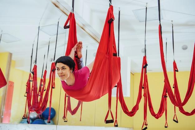 ハンモックでヨガフライを練習する若い美しい女性。飛行、フィットネス、ストレッチ、バランス、運動。