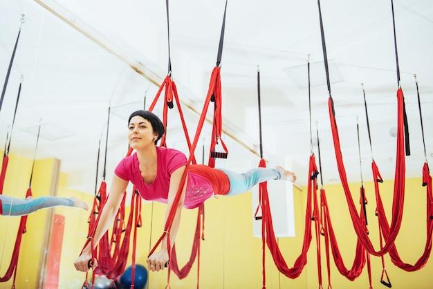 明るいスタジオでハンモックでヨガフライを練習して若い美しい女性。精神的および肉体的健康の概念。