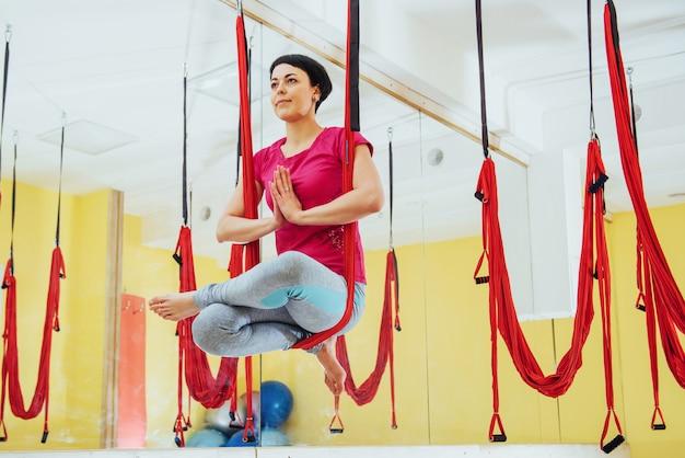 ハンモック、心身の健康の概念とヨガフライを練習する若い美しい女性。