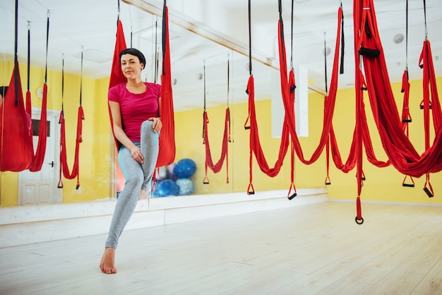 Young beautiful woman practicing yoga fly with a hammock, the concept of mental and physical health.