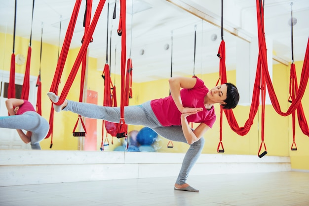 Young beautiful woman practicing yoga fly with a hammock . flying, fitness, stretch, balance, exercise.