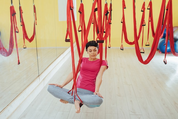 Young beautiful woman practicing yoga fly with a hammock