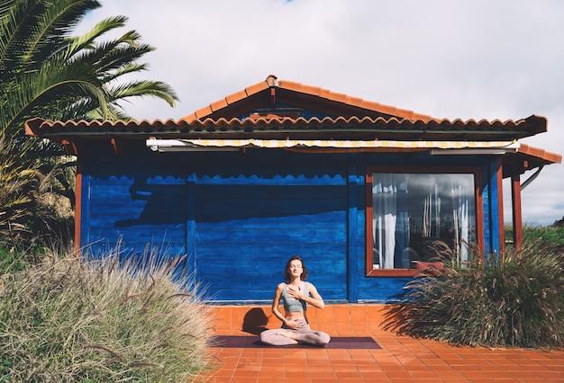 Молодая красивая женщина упражнениями йоги на земле возле синего деревянного дома