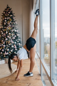 Young beautiful woman practicing yoga, split, twine and sport gymnastic exercises near the window.