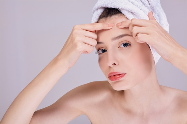 Young beautiful woman presses acne on her forehead.