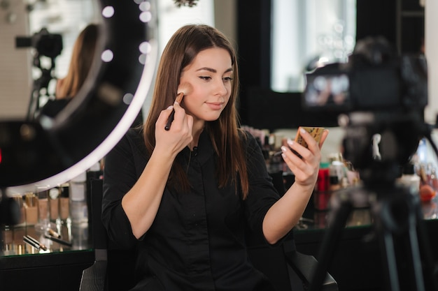 Young beautiful woman and professional beauty make up artist blogger recording makeup tutorial in studio