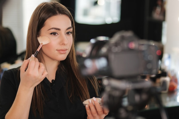 Young beautiful woman and professional beauty make up artist vlogger recording makeup tutorial in studio