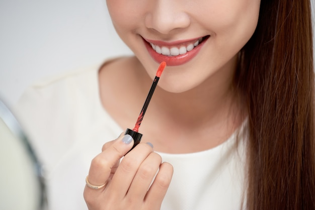 Young beautiful woman professional beauty vlogger or blogger applying lipstick cream to her mouth, doing a make up tutorial