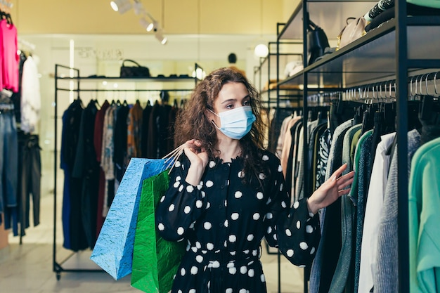 Young beautiful woman in a protective mask on her face, chooses clothes in the store