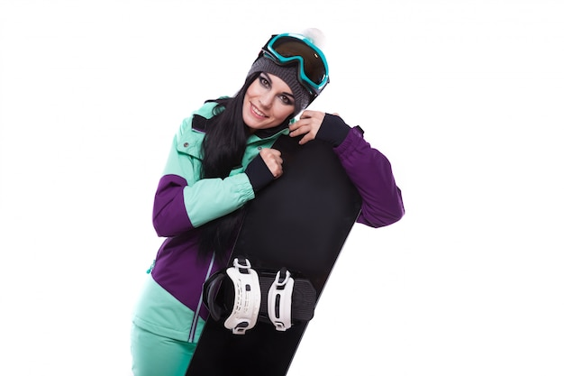 Young beautiful woman in purple ski suit hold snowboard