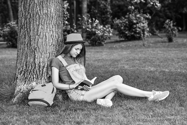 Young beautiful woman reading book at the park