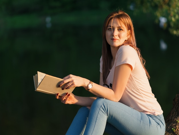 Young beautiful woman reading a book on the river bank during sunset