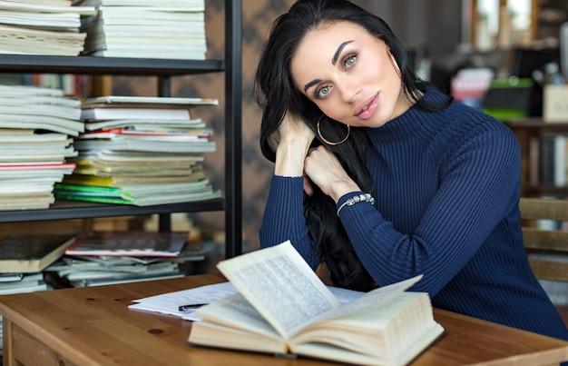 Молодая красивая женщина, читая интересную книгу в кафе.