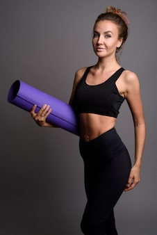 Young beautiful woman ready for gym against gray wall