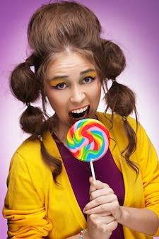 カラフルなロリポップを食べる準備ができて若い美しい女性
