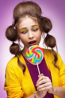 다채로운 막대 사탕을 먹을 준비가 젊은 아름 다운 여자