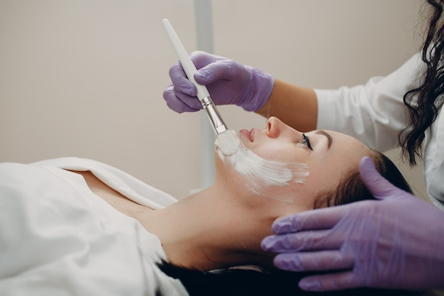 Young beautiful woman receiving white facial mask in spa beauty salon.