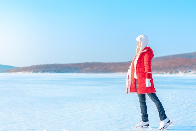 Young beautiful woman in red coat and figure skates stands on the frozen sea